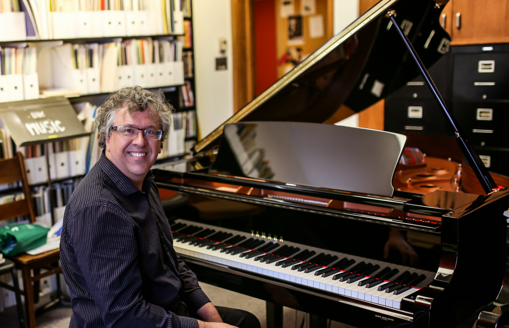 Pianist Corey Hamm sitting at the piano in his office at UBC