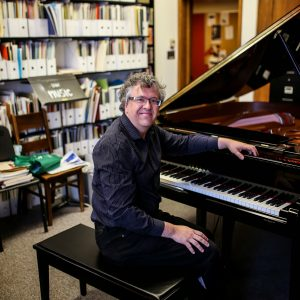 pianist Corey Hamm posing at the piano in his office